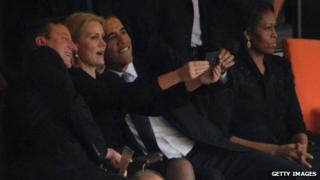 David Cameron, Helle Thorning-Schmidt and Barack Obama posing for a selfie, while Michelle Obama sits separately