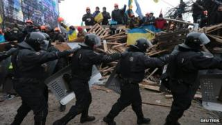 Riot police march past protesters in Independence Square, Kiev, on 11 December 2013