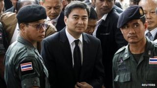 Democrat Party leader and former prime minister Abhisit Vejjajiva (centre) arrives at Bangkok criminal court in Bangkok, 12 December 2013