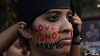 """An Indian gay-rights protester has """"love is not a crime"""" written on her face."""