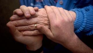 A younger person holding an older person's hands