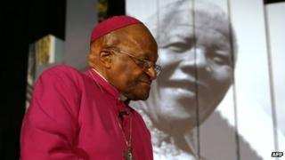 Archbishop Tut before an image of Nelson Mandela