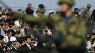 Japanese Prime Minister Shinzo Abe (bottom 3rd L) reviews Japan Self-Defence Forces troops during the annual SDF ceremony at Asaka Base near Tokyo on October 27, 2013