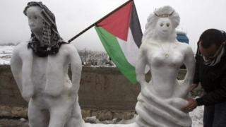 A Palestinian man makes snow sculptures in Jerusalem on December 14, 2013