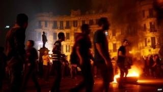 Egyptian protesters set fire to wood at Talaat Harb Square in Cairo at a protest against military trials for civilians (26 November 2013)