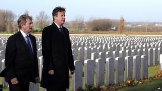 British Prime Minister David Cameron, right, and Irish Prime Minister Enda Kenny walk through rows of World War One graves as they visit Tyne Cot Cemetery in Zonnebeke, Belgium on Thursday, Dec. 19, 2013.
