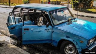 A man rests in a car front the Moncada Barracks in Santiago de Cuba, on July 23, 2013
