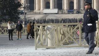 Policeman walks on white powder left from the fire extinguisher in St Peter's Square (19 December 2013)