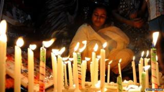 Bangladeshi garment workers and relatives of victims of the Rana Plaza building collapse hold candles during a memorial