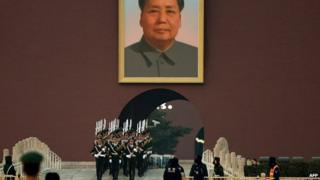 Chinese para-military police march beneath a portrait of late leader Mao Zedong beside Tiananmen Square in Beijing on December 13, 2013
