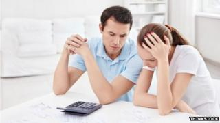 couple looking worried with calculator