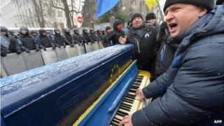 A man plays piano and sings songs in front of riot police as protesters picket Viktor Yanukovych's presidential office in Kiev