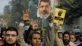 Supporters of former president Mohammed Morsi hold up a poster of him, 20th December