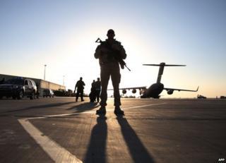 A US soldier stands guard near a plane on a runway at Kandahar air base, 8 December