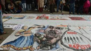 """In this photograph taken on December 30, 2012, Indian bystanders look at a banner featuring images of """"government and rapists"""" as it lies on a road in New Delhi"""