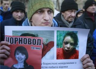 Activists hold photo of journalist and activist Tetyana Chornovol as they rally outside the Ukrainian Interior Ministry in Kiev on 26 December, 2013