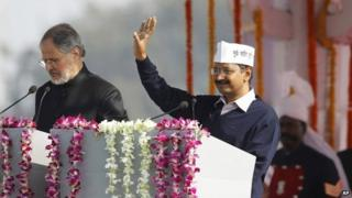 Arvind Kejriwal, right, waves to the crowd at his inauguration as chief minister of Delhi, India, 28 December 2013