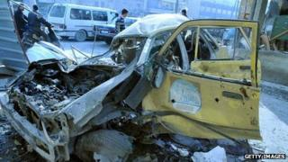 Damaged cars are seen after a regime helicopter dropped barrel bombs on a market square