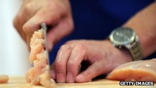 man cutting chicken