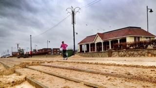Jogger on sand covered Felixstowe promenade