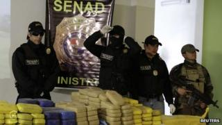 Police officers present evidence confiscated from an illegal airfield in a rural northern area used for drug trafficking on 23 August, 2013