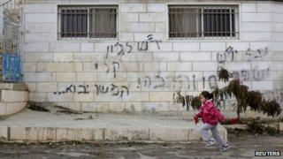 """A girl runs past graffiti on a house in the West Bank village of Dahiyat al-Zira that reads: """"Regards to John Kerry - to be continued"""" (31 December 2013)"""