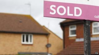 """A """"sold"""" sign outside a house"""