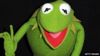 Kermit the frog holds up a finger as if to make a point.
