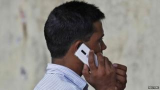 A man speaks on a mobile phone at a marketplace in New Delhi June 18, 2013