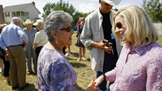 US Senate candidate Liz Cheney, far right, talks to supporters as her opponent Senator Mike Enzi, left, also makes the rounds during a tea party rally in Emblem, Wyoming 24 August 2013