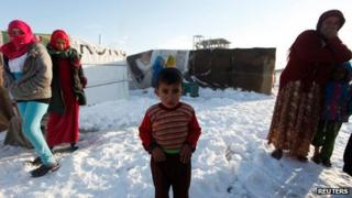 A child refugee from the northern province of Raqqa in Syria, reacts from the cold weather in a Syrian refugee camp beside the Lebanese border town of Arsal, in eastern Bekaa Valley (December 12)