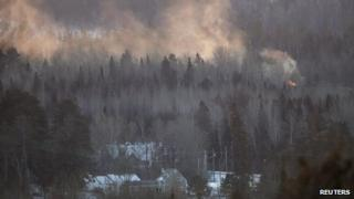 Flames and smoke are seen at the site of a train derailment in Wapske, New Brunswick 8 January 2014
