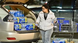 Charleston resident Niru Parikshak loads up the back of her car with bottled water 9 January 2014