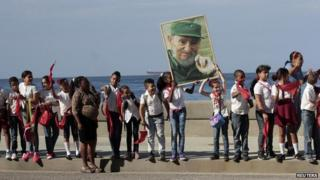 School children stand in Havana while holding a photograph of Cuba's former President Fidel Castro