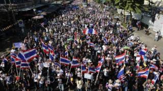 Protesters waving flags block a road in Bangkok