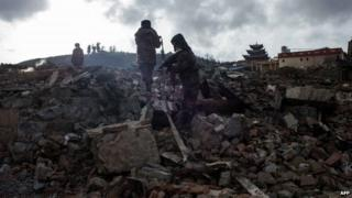 This picture taken on 12 January 2014 shows rescuers working on the wreckage of damaged houses in an ancient Tibetan town of Gyalthang, known in Chinese as Dukezong, in Shangri-La, southwest China's Yunnan province after a fire flattened two thirds of the town's old centre