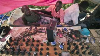 Men running a makeshift mobile phone charging station at a camp for displaced people in South Sudan
