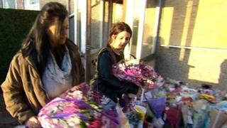 People leaving flowers outside the house the victims died