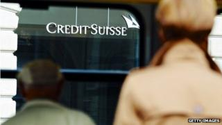 People walking towards a Credit Suisse sign