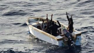 This handout picture released by the EU Navfor on 13 January 2012 shows six Somali men surrendering to members of a EU NAVFOR vessel