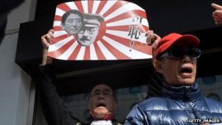 A protester in Hong Kong holds up a sign with photos of current Japanese Prime Minister Shinzo Abe and World War II Prime Minister Hideki Tojo.