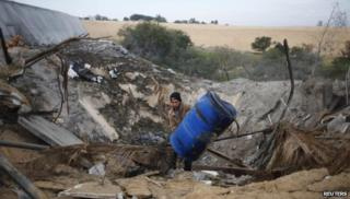 A Palestinian man in the Gaza Strip inspects a site which witnesses said was hit in an Israeli air strike on 14 January 2014