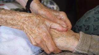 Carer holding elderly person's hands
