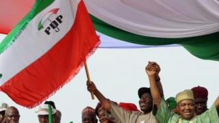 Nigerian President Goodluck Jonathan (C) and Vice President Namadi Sambo (R) wave the People's Democratic Party (PDP) flag on the podium at the start of Goodluck Jonathan's presidential campaign at the Lafia Township Stadium in the north central town of Lafia, Nasarawa state on 7 February 2011