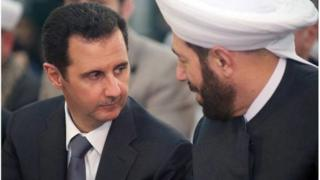 Bashar al-Assad (L) speaking with Syrian Grand Mufti Ahmed Hassun, posted on the government's Facebook page on January 12
