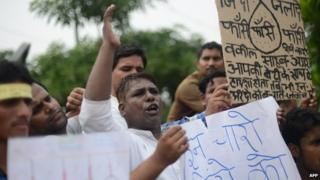 Indian men stand outside a court in India demanding the death penalty of four men convicted of rape and murder in Delhi.