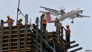 Construction workers erect scaffolding at the site of a metro station as a SpiceJet Airlines aircraft flies past in the southern Indian city of Chennai