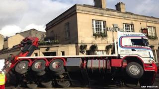 A lorry rests on the walls of the Lamb and Lion pub in Bath