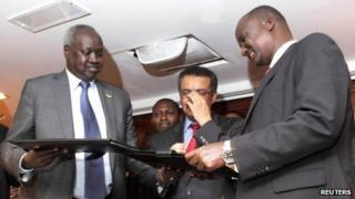 South Sudan's leader of the government's delegation Nhial Deng Nhial (L) exchanges a signed ceasefire agreement with the head of the rebel delegation General Taban Deng Gai (R)