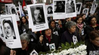 """Demonstrators hold up images of their relatives, who were victims of human rights abuse during the former General Augusto Pinochet years, in front of the """"La Moneda"""" Presidential Palace during a rally in Santiago September 11, 2013."""